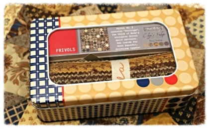 A QUILT KIT; FRIVOL # 3-HERITAGE - CONTAINS ELIZA'S INDIGO FABRIC BUNDLE BY MODA FABRICS, YOUR PATTERN, A BONUS PATTERN AND A SURPRISE, ALL PACKAGED IN A COLLECTIBLE TIN THAT MATCHES THE FABRIC INSIDE.