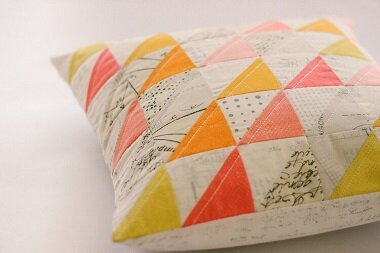 Photos courtesy of Zen Chic/ Moda Fabrics and Supplies  Designer Brigitte Heitland's signature modern style shines in even the simplest triangle block. Plugging in modern prints and low volume blenders changes the look of traditional piecing in a most pleasing way. Pictured is her pillow done in half square triangles with prints from her  Spotted  and  More Paper Modern Backgrounds  fabric collections.