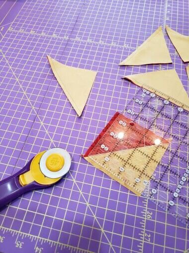 Flip the blocks open and either lightly finger press or use your iron to lightly press. Be careful not to over press as these triangles are cut on the bias and will stretch. Starch or Best Press on the fabric helps quite a bit.  Place a ruler on the block keeping the 45-degree diagonal line over the diagonal seam. Trim each side of your squares to 3 1/2""