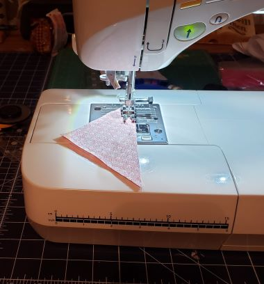 "Place right sides together and sew together with a 1/4"" seam on the long edge to create a half square triangle (HST)."