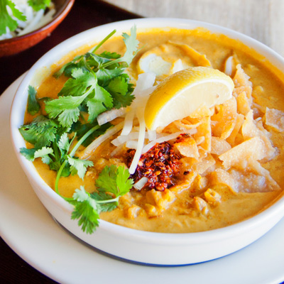 Oh Noh Kauswer  (Coconut Chicken Noodle Soup) Burmese style coconut noodle soup with chicken, onions, eggs, cilantro, wonton, chips, lemon, and topped with chili.