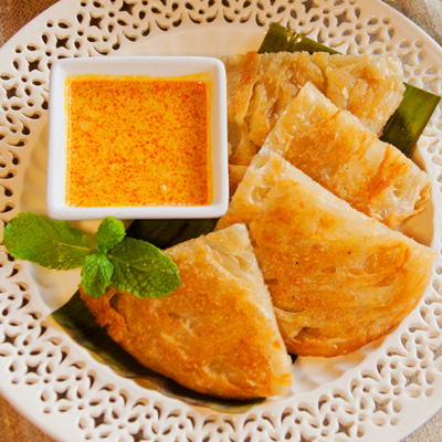 Platha Dip  Homemade multi-layered bread served with a coconut chicken curry sauce.