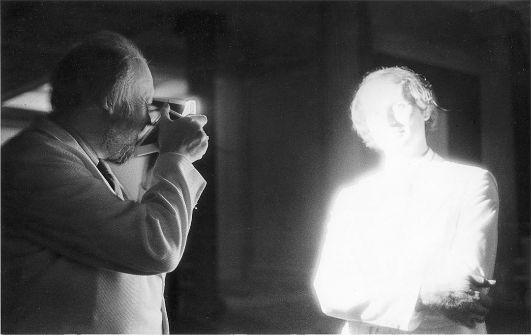 """Jonathan Williams photographing Ray Kass at the opening of """"I Will Save OneLand Unvisited; 11 Southern Photographers,""""Corcoran Gallery of Art, Washington, D.C. PHOTOGRAPH: SALLY MANN, 1978. Copyright © 2014 by Sally Mann. All Rights Reserved."""