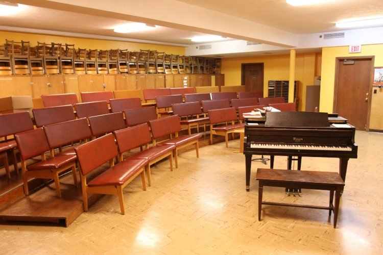 Choir Practice Room - Large private choir practice room that is often used by a music groups of up to 50 people for rehearsals prior to events or on scheduled times. Seating is tiered and a grand piano is available.