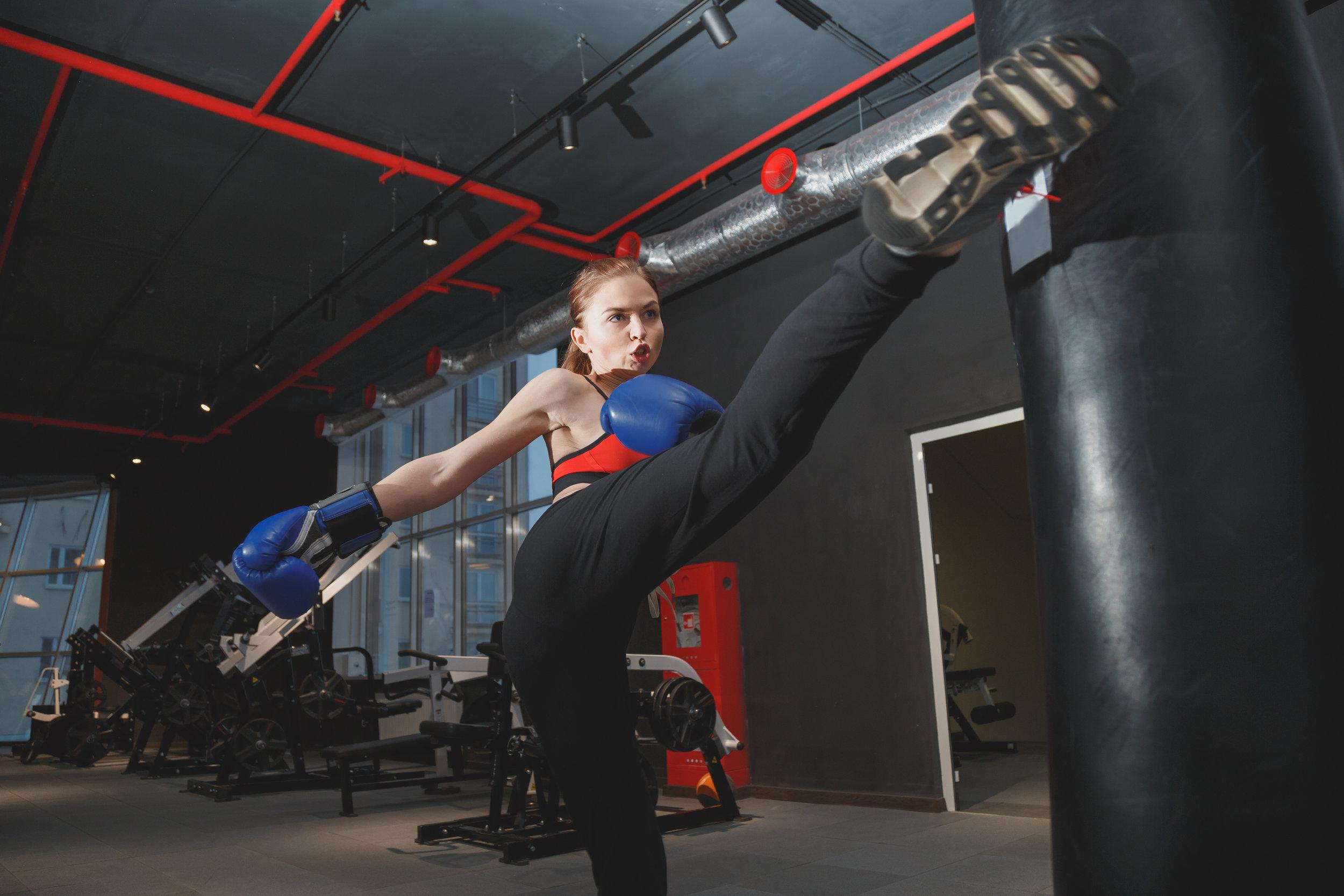 kickboxing-woman-punching-kicking-bag-at-the-gym-PVJ9KGK.jpg