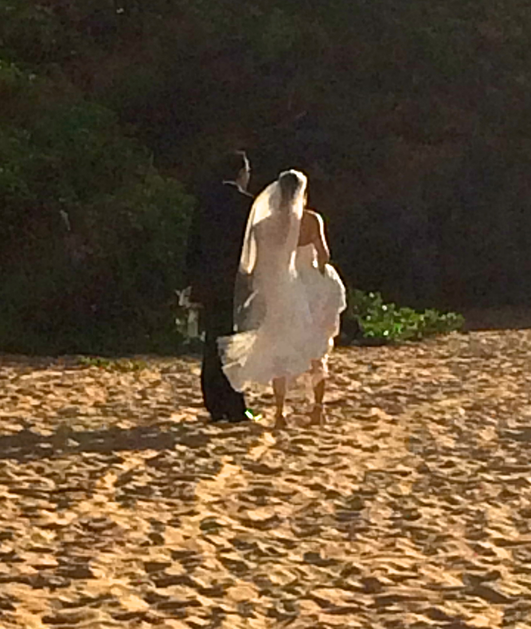 Couple walking to their wedding on the beach at Four Seasons Resort Maui at Wailea.  Photo by Rebecca Garland.