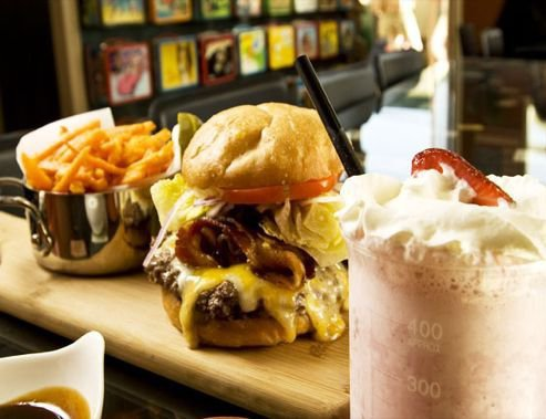 Burger, fries and a shake with old school lunchboxes in the background. Photo by Lunchbox Laboratory.