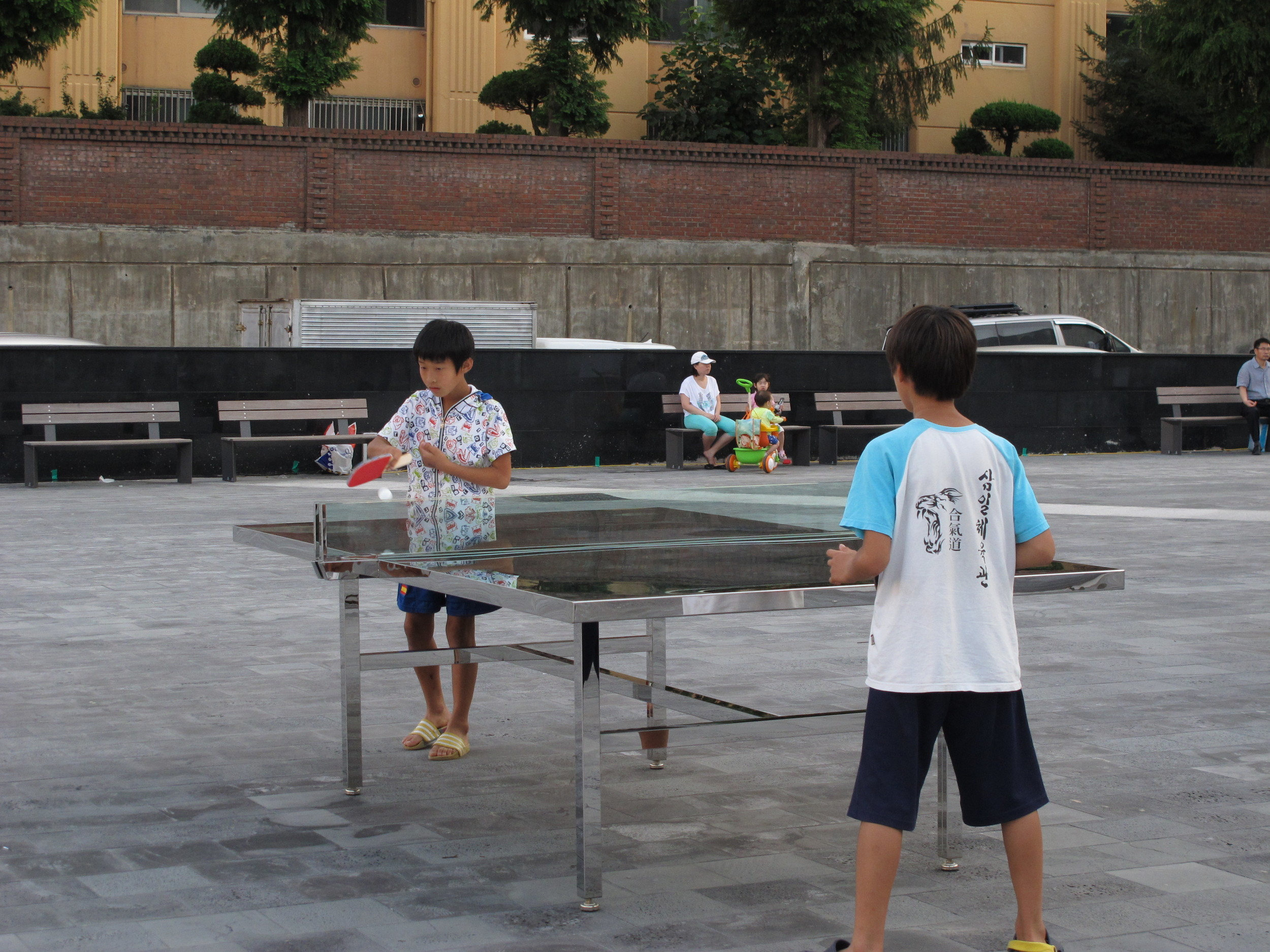 Children play with Rirkrit Tiravanija's artwork Untitled 2012 (who if not we should at least try to imagine the future, again) (remember Julius Koller) which consists of 14  pingpong tables with two nets each, referencing North and South Korea