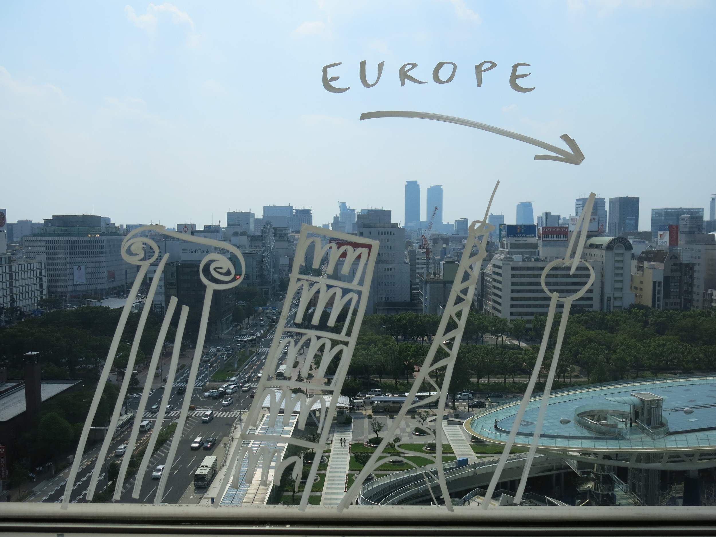 Romanian artist Dan Perjovschi's    The Top Drawing,    2013   on the window of the 11th floor-viewing balcony of the Aichi Arts Center.