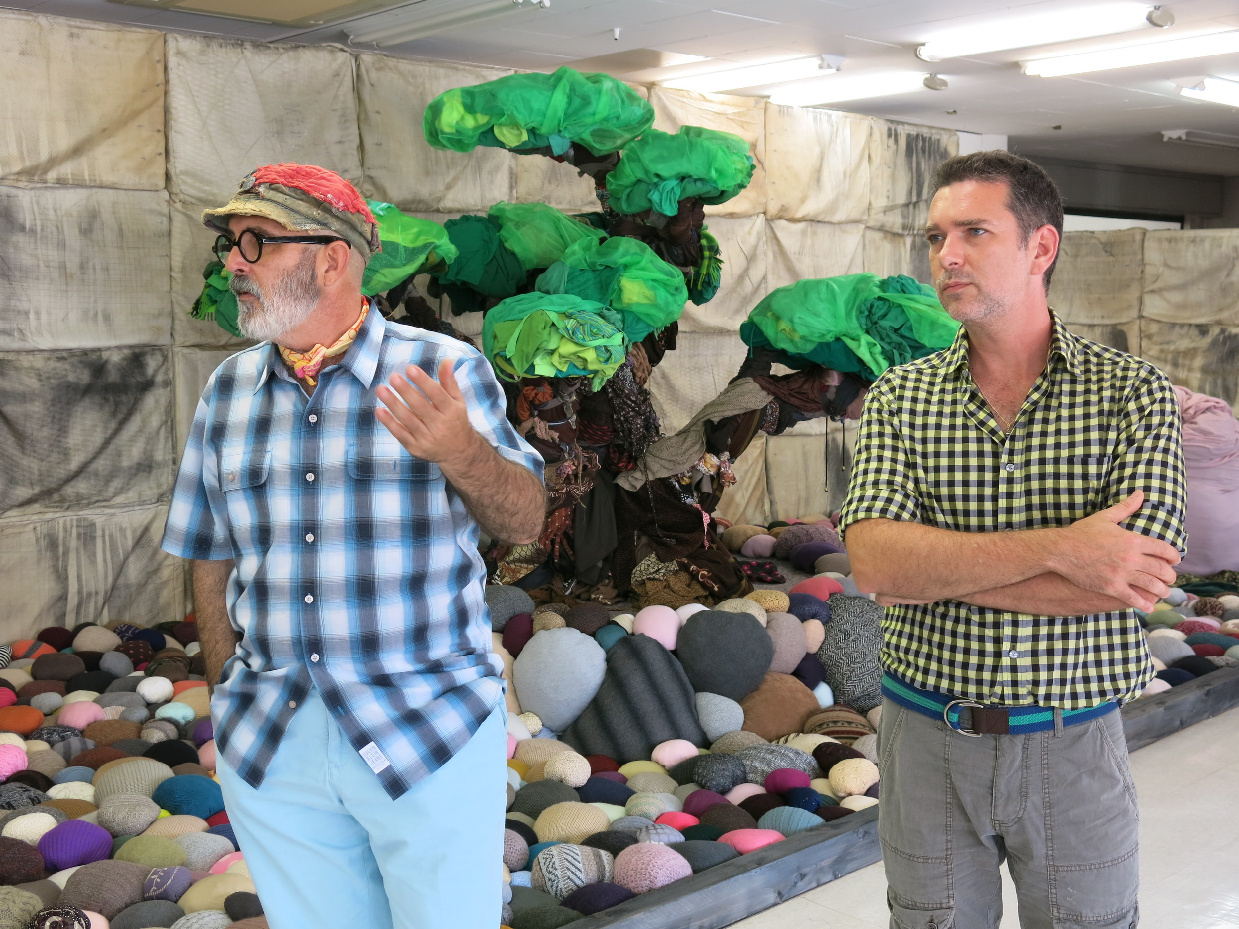 LA-based artists   Alain Guerra and Neraldo de la Paz, collectively known as    Guerra de la Paz   , pictured in front of  Secret Garden , 2013 on the unused top floor of a shopping mall in the Higashi Okazaki Station.     While they generally source their materials from the waste bins of second-hand goods shipping companies in Miami's Little Haiti, for their site-specific work at the Aichi Triennale they use clothes from the factories in Ozahaki.   Okazaki site.