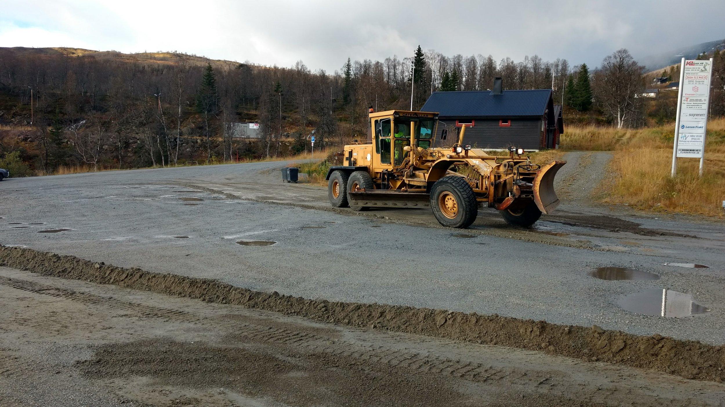 Her er Per Kåre Haug i gang med veghøvelen til Sogndal kommune på parkeringsplassen ved SIL-hytta.