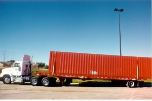 Container loaded on a tilt-bed Landoll trailer for ground-level delivery