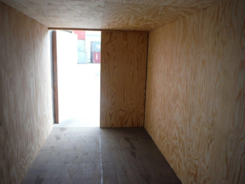 Container office with insulation and plywood interior walls, doors still functional
