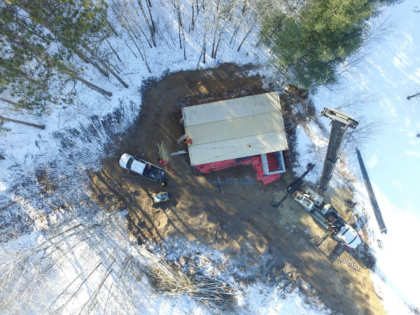 Drone view of 3 container sitting on the foundation of a house with the crane next to the house