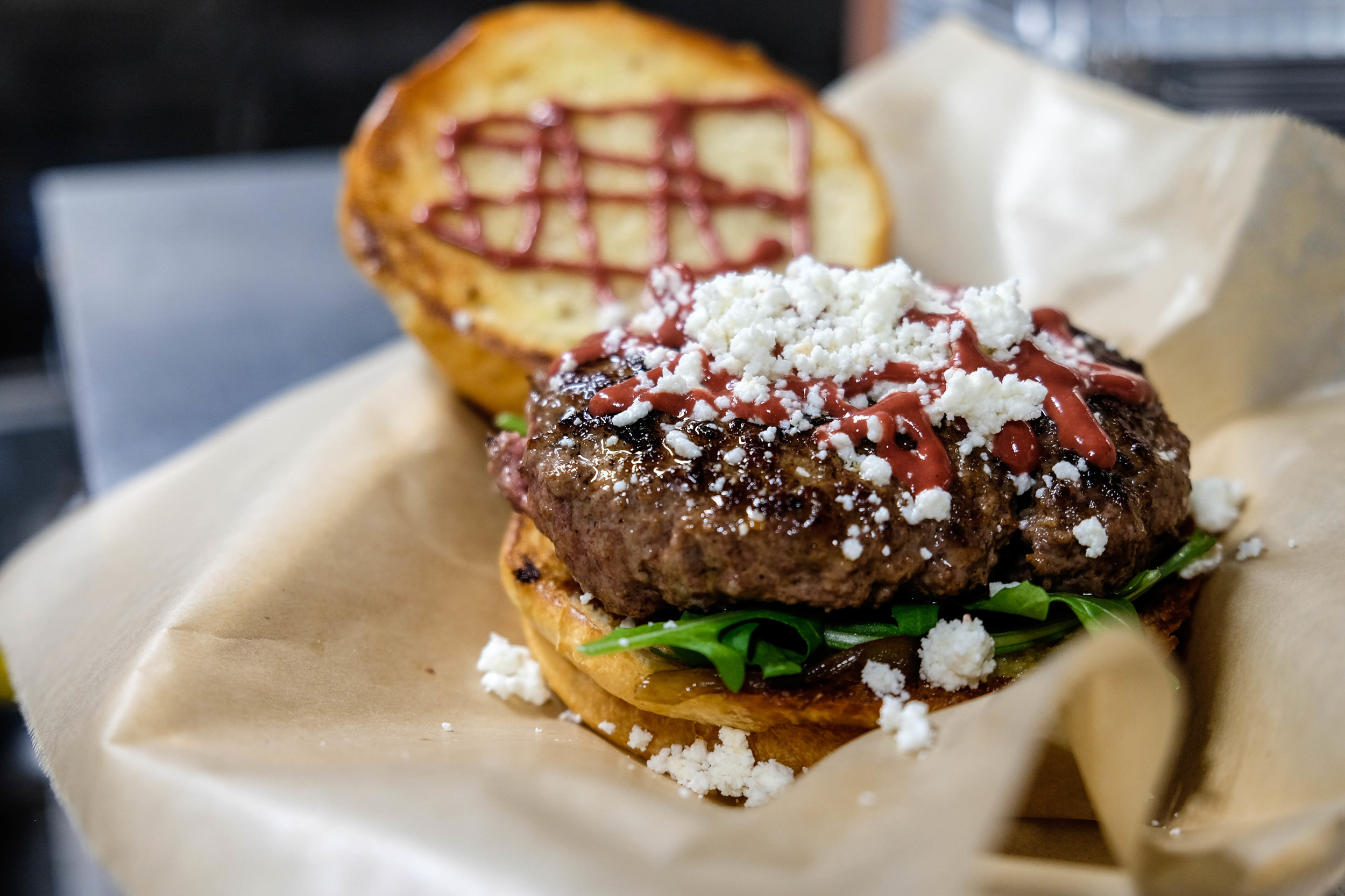 The Contemporary Burger. Beef patty, smoked chèvre, caramelized onion, arugula, beet dijon.