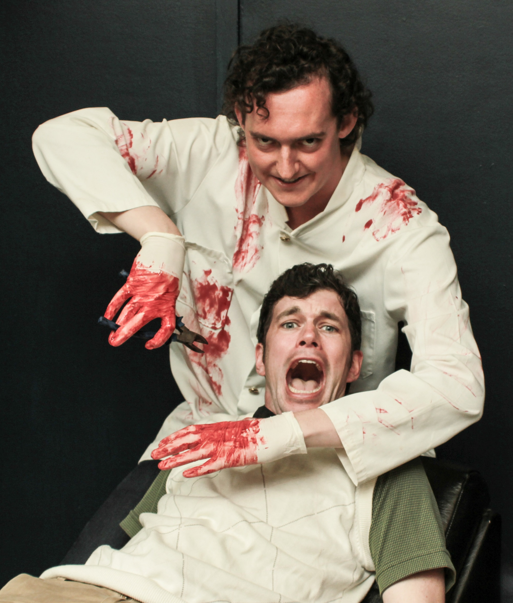 Seymour (Owen Measday, front) finds himself at the mercy of sadistic dentist Orin Scrivello (Luke Daly) in  Little Shop of Horrors .
