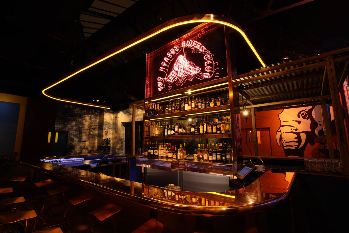 The Courtyard Bar was at the heart of the Double Club experience. The space was divided into four slices: two western and two Congolese, and was covered with a glass roof lending it a special outdoor feeling.  The Congolese bar boasts imported wood and corrugated iron from Kinshasa. The Western bar, by contrast, is a solid copper monoblock lit up by neon signage announcing the Two Horses Riders Club — for people who enjoy riding two horses simultaneously.