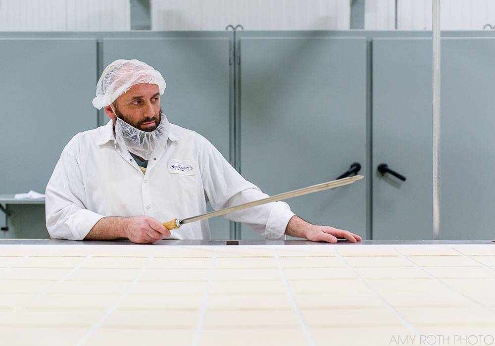 A worker inspects cut matzoh squares for defects before they go into the oven at the Manischewitz plant in Newark, NJ. Photography by Amy Roth, on assignment for Edible Jersey.