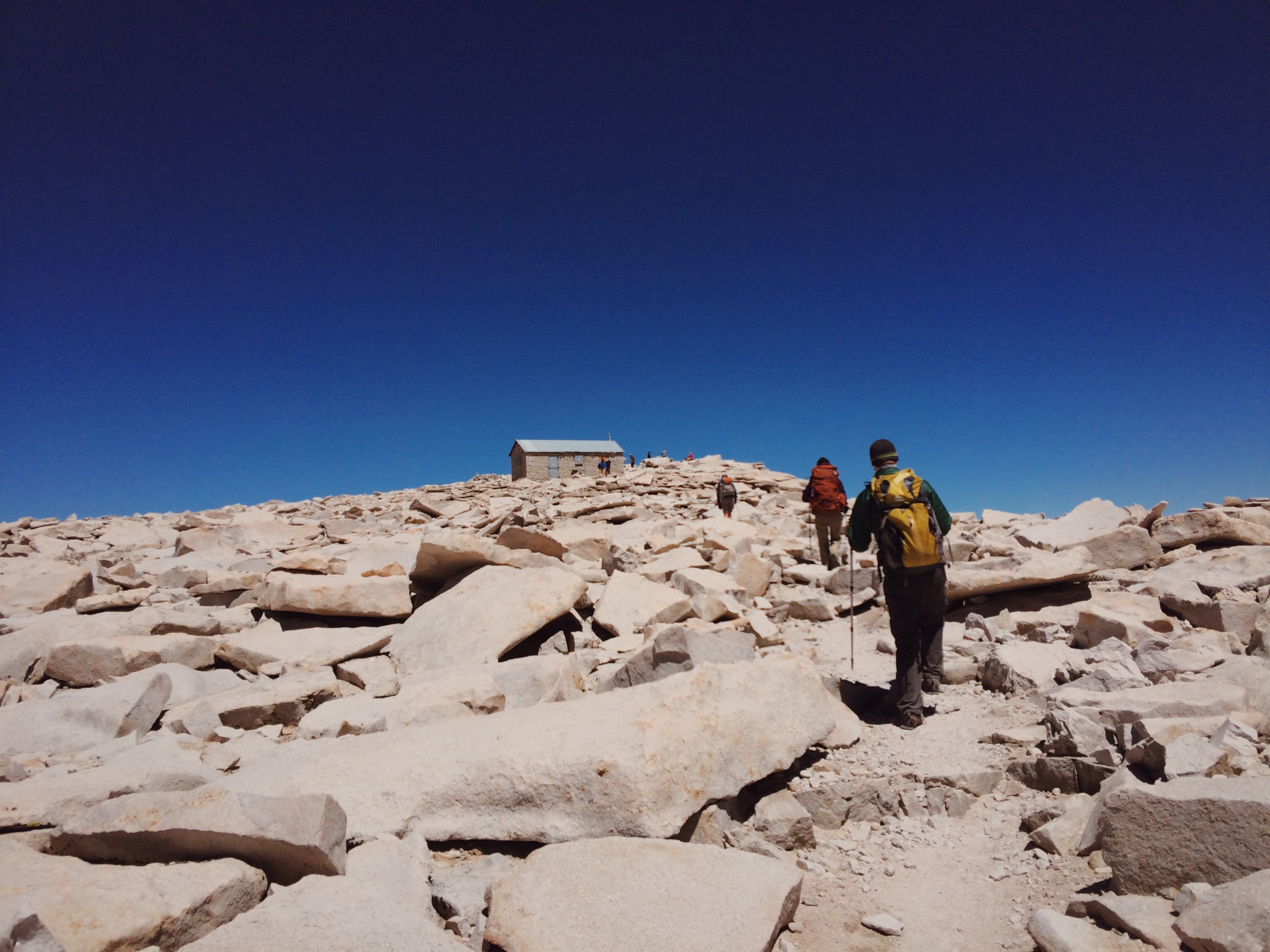 Taking the last few steps to the summit of Mt. Whitney (14,505'), the southern terminus of the JMT. Yes, the sky really was that blue.