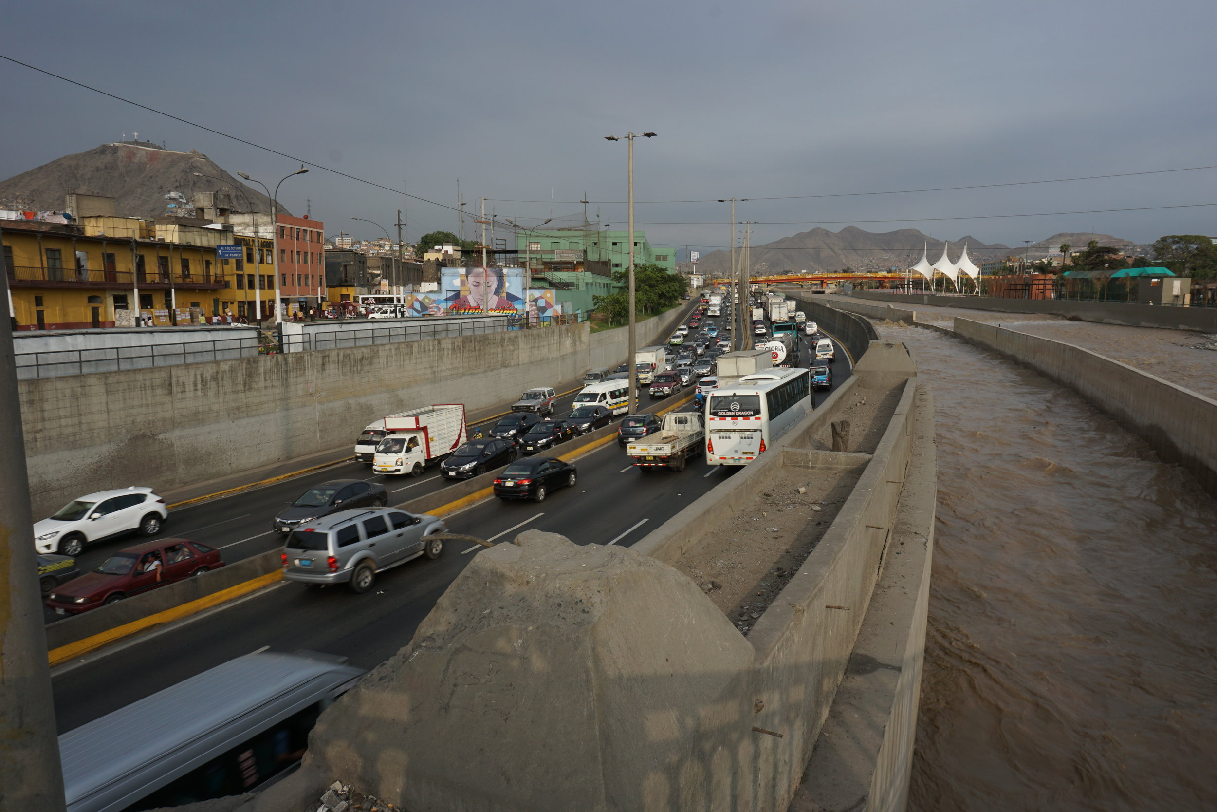 Just steps from the Plaza Mayor, a view of Lima's slums and highway from a bridge above the Rio Rimac.