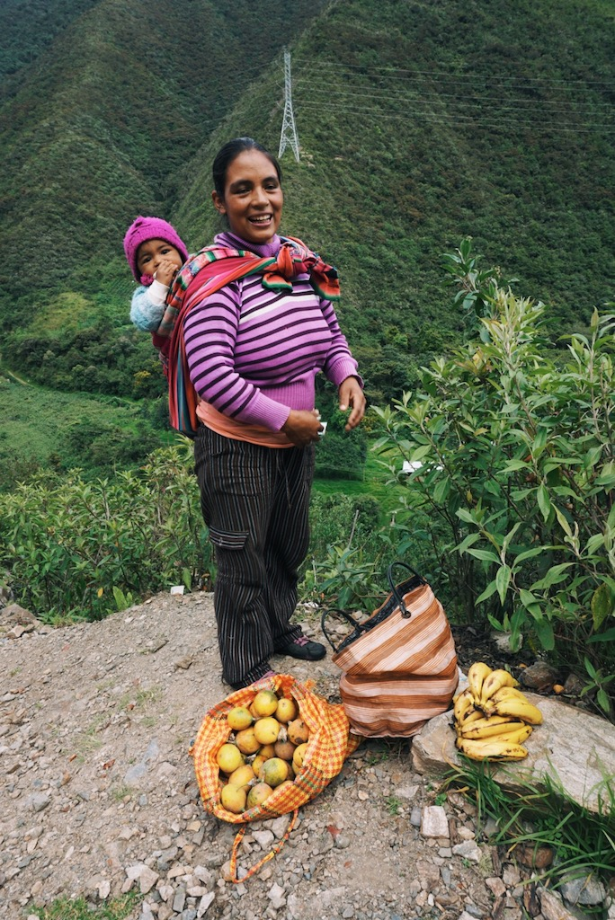 A fruit vendor selling passion fruit and bananas she grows down a steep path and next to the river.