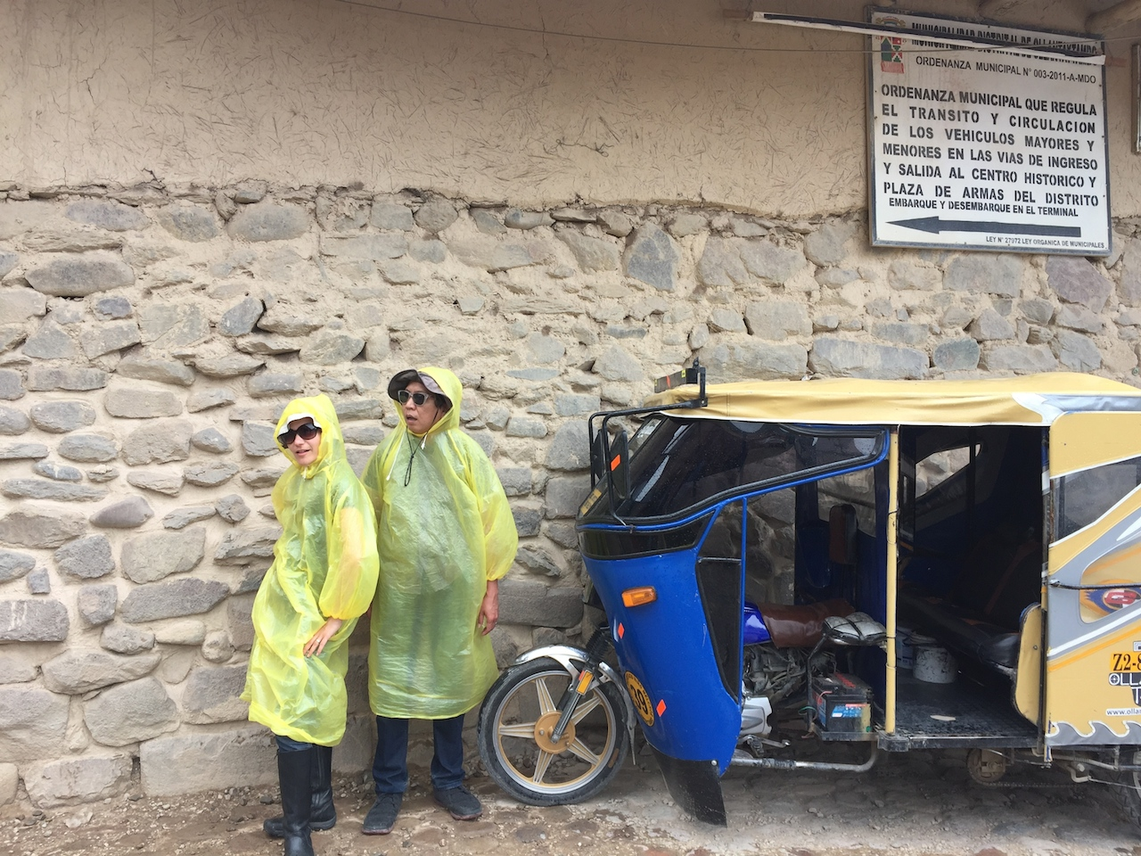 The travelers sporting fashionable disposable ponchos in Ollantaytambo.
