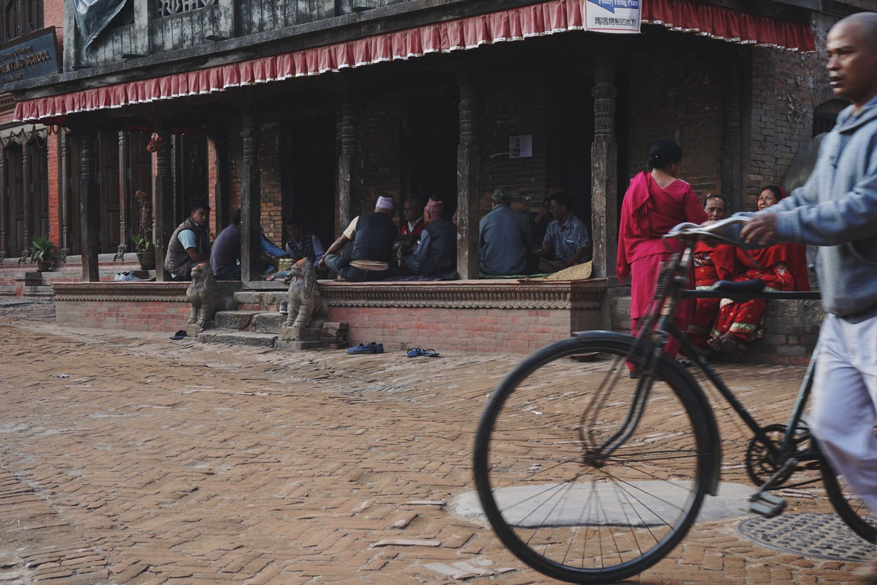A gathering of Nepali men under the eave of building near Durbar Square