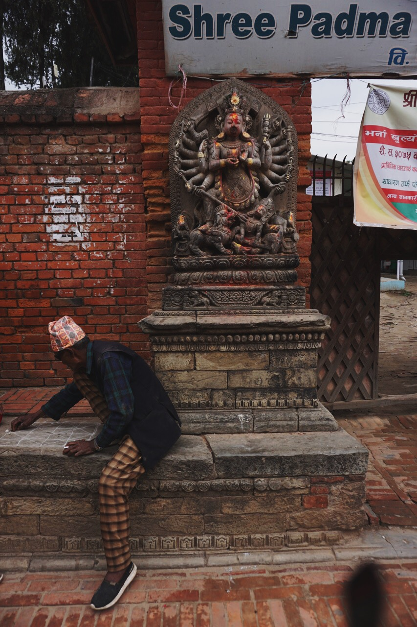 Shiva looks on over a man in a traditional Nepali hat
