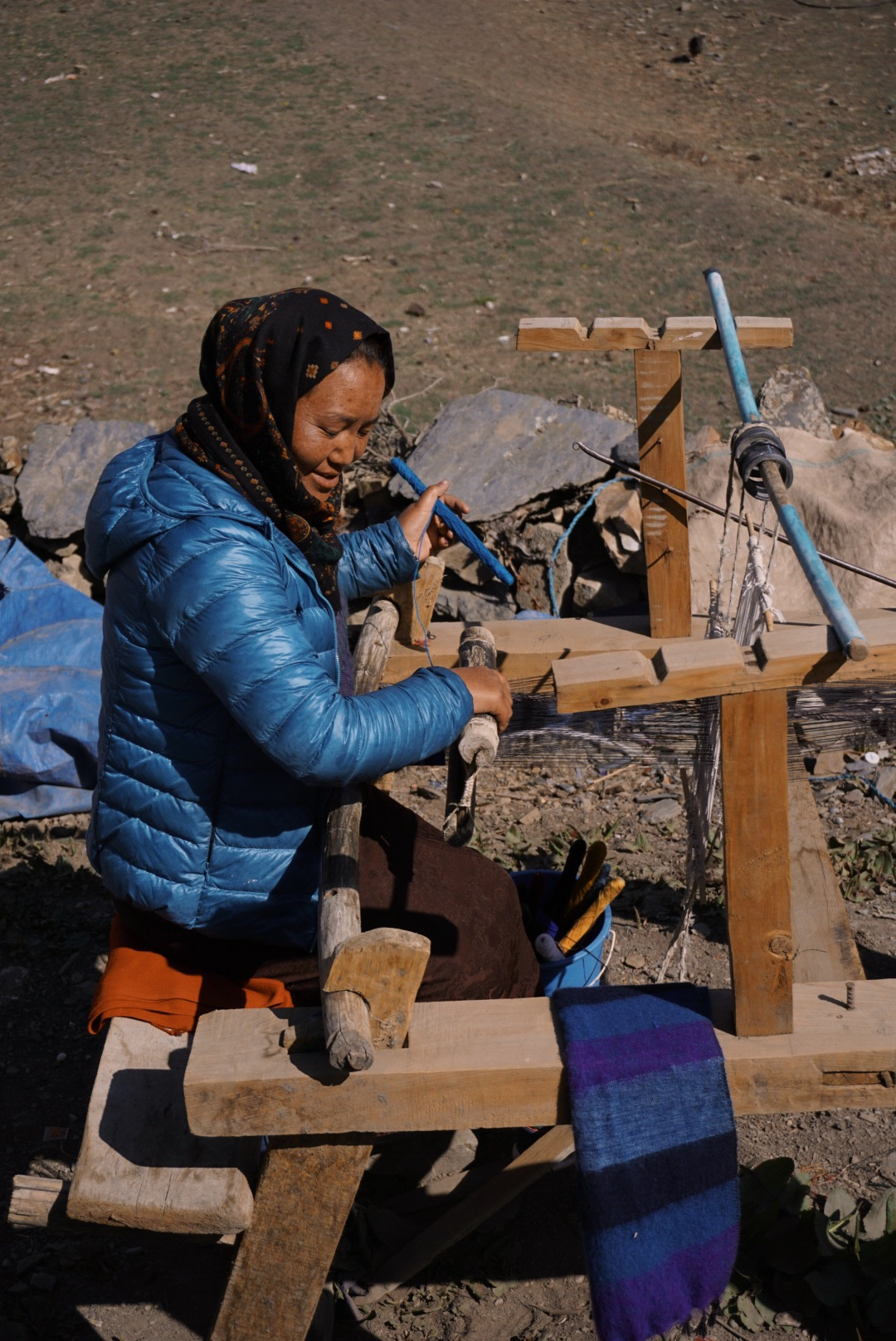 This is Korchu in the pilgrimage site of Muktinath. She weaves scarves out of yak wool using this traditional wooden loom. A large scarf takes her two days.
