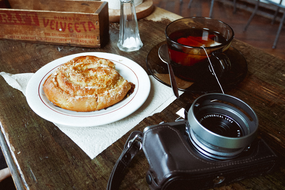 A Fuji X70, a tea and a bun shot with a Panasonic flat screen TV