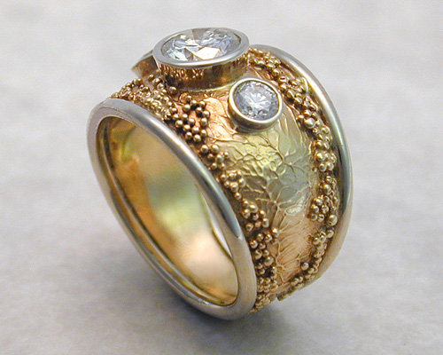 Handcrafted free-form engagement band with spherical granulation and branch like textures.