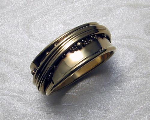 Free-form, wrap-around wedding ring with spherical granulation.