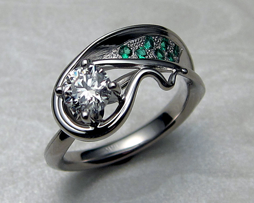 Asymmetrical, free-form, engagement ring, with diamond and emeralds.