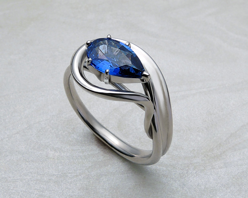 Pear shaped engagement ring with cornflower blue sapphire.