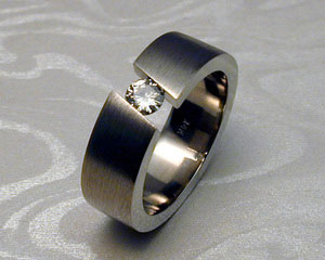 Tension set diamond band, with diagonal opening.
