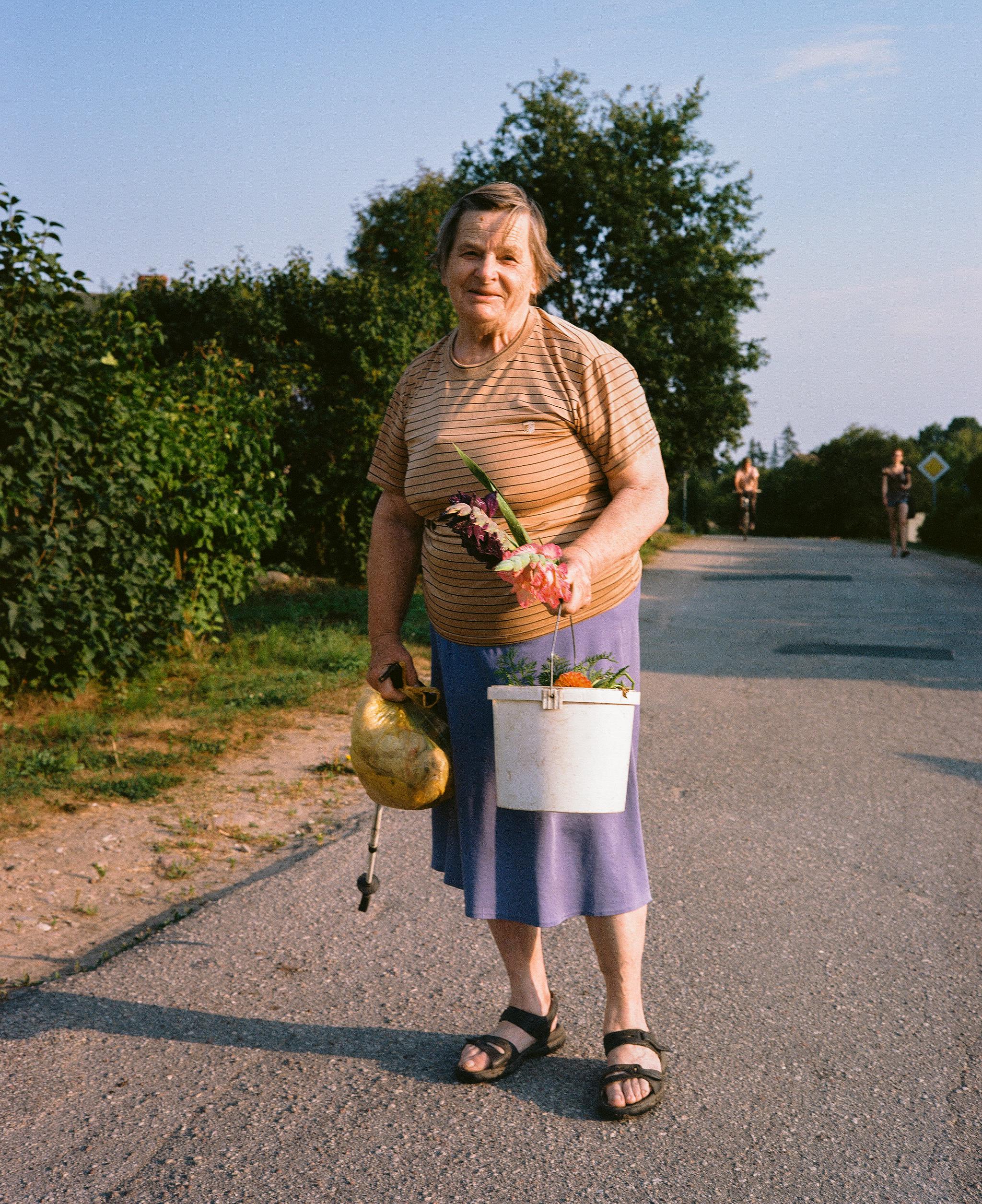スロベニア、ペリシの村で出会ったおばあさん。午後7時、日課である自分の庭の草むしりを終えて家に帰る途中。「ほら、うちでこんなに綺麗に咲いたのよ」と摘み取ったばかりのルピナスを見せてくれた。