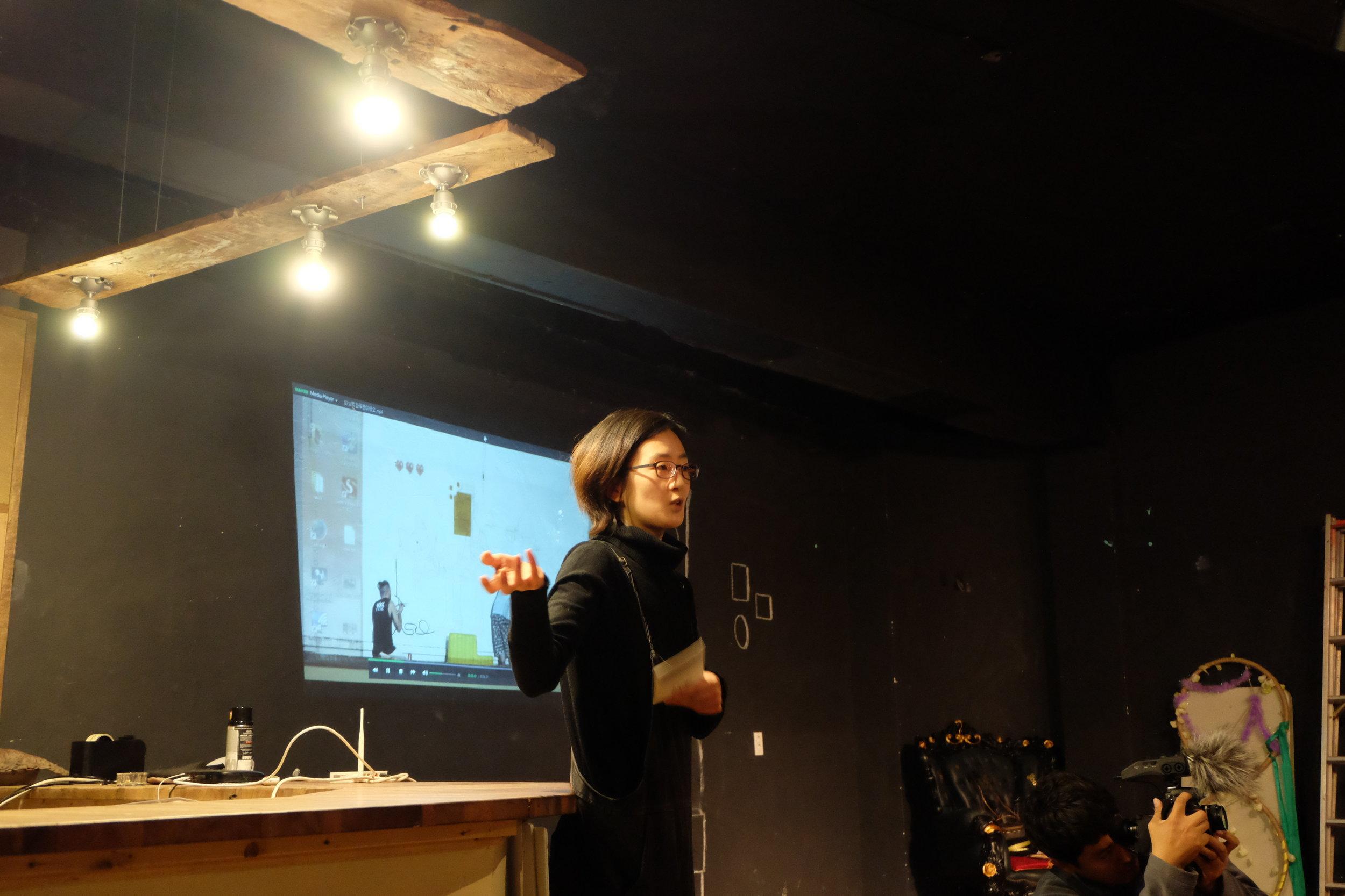 コミュニティーに根付いたストリートアート的活動について説明中。