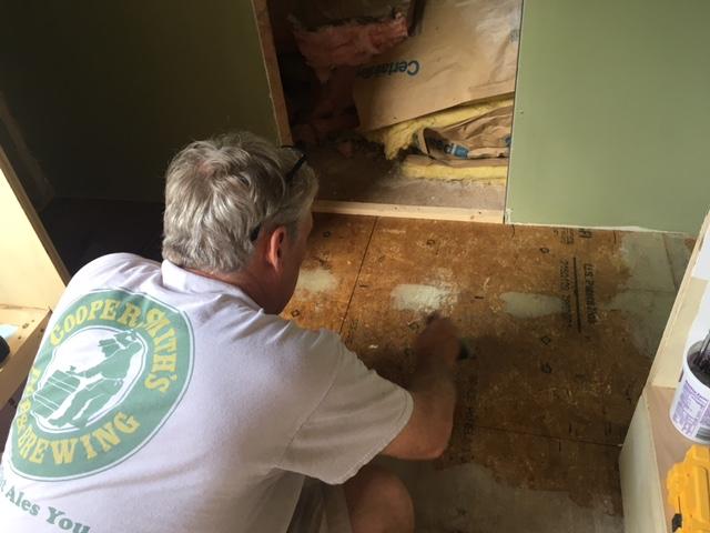 applying contact cement on floor.JPG