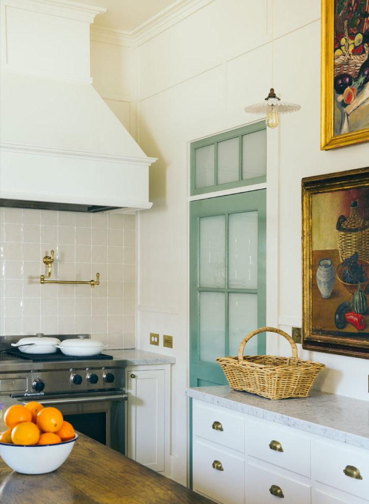 kitchen-marble-countertops-white-cabinetry-oil-paintings-wicker-basket-green-door-brass-pulls-sorrento-beach-house-anna-spiro-interior-design-751x1024.jpg