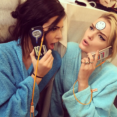Kendall personalized her phone case with three stickers, which means that this phone case is worth at least $175. Blonde model on the right clearly thought these were cheap enough to be disposable stickers since she just wasted one on her forehead...