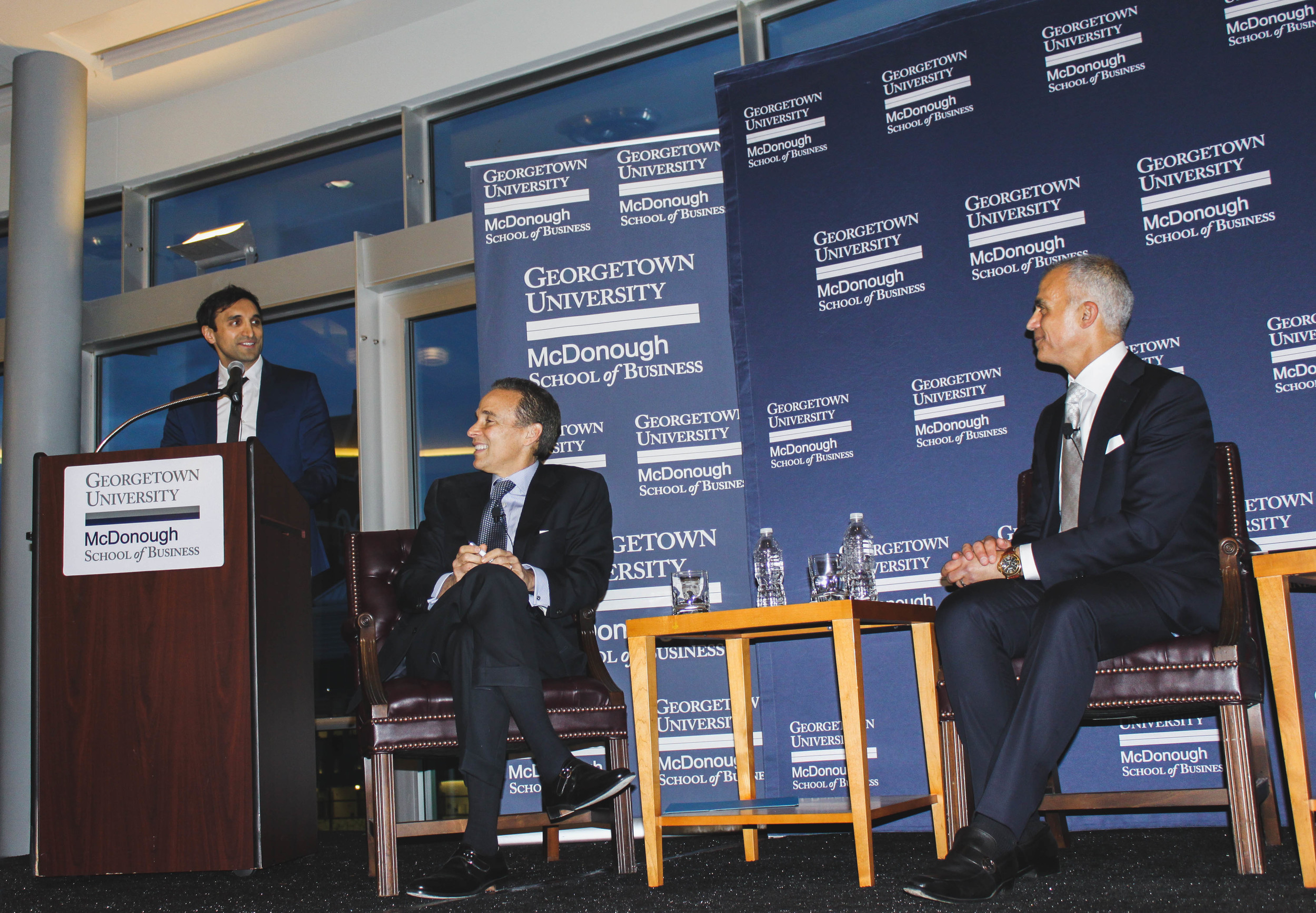 Ajaz Ahmed at the podium with Professor Ricardo Ernst and Mark Del Rosso