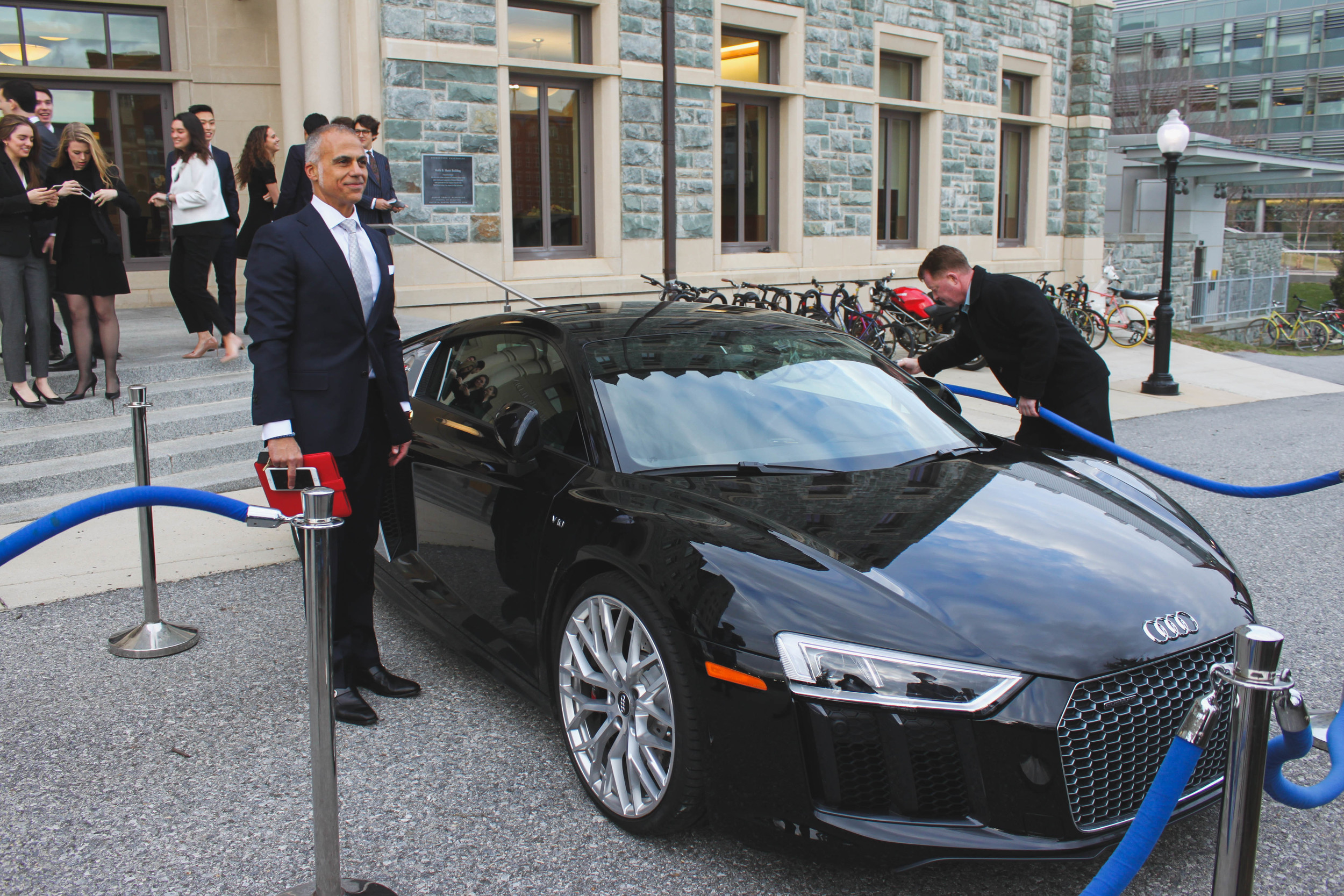 Mark Del Rosso posing with the Audi R8 in front of the McDonough School of Business