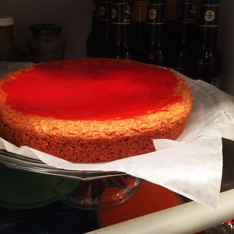 Strawberry lemonade jam setting up on the lemon layer cake.