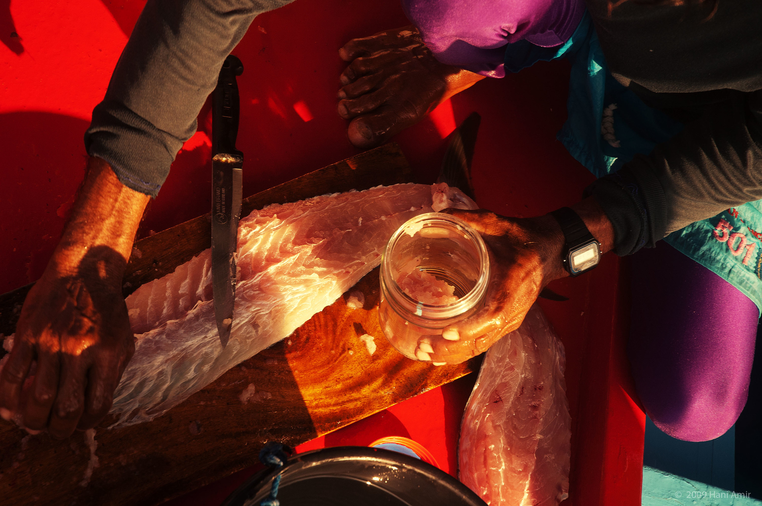 A fisherman collects the chum he has createdinto a water-tight glass jar