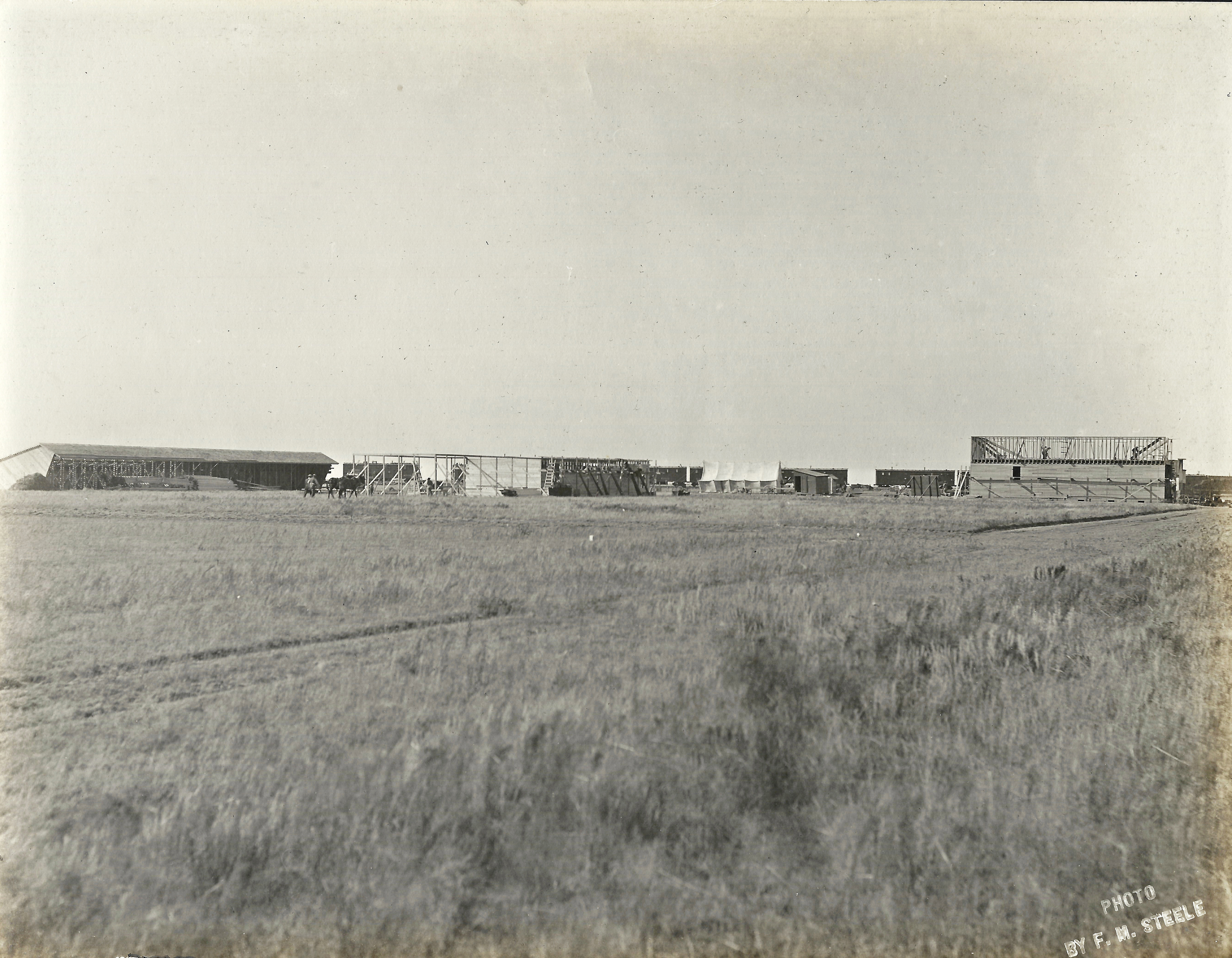 Construction on the new town, Sublette - 1912   In the background you will notice the rail cars in use on the newly laid track. The buffalo grass has been cut short to mark the new main street with construction on the first building in Sublette, The Cave Mercantile.
