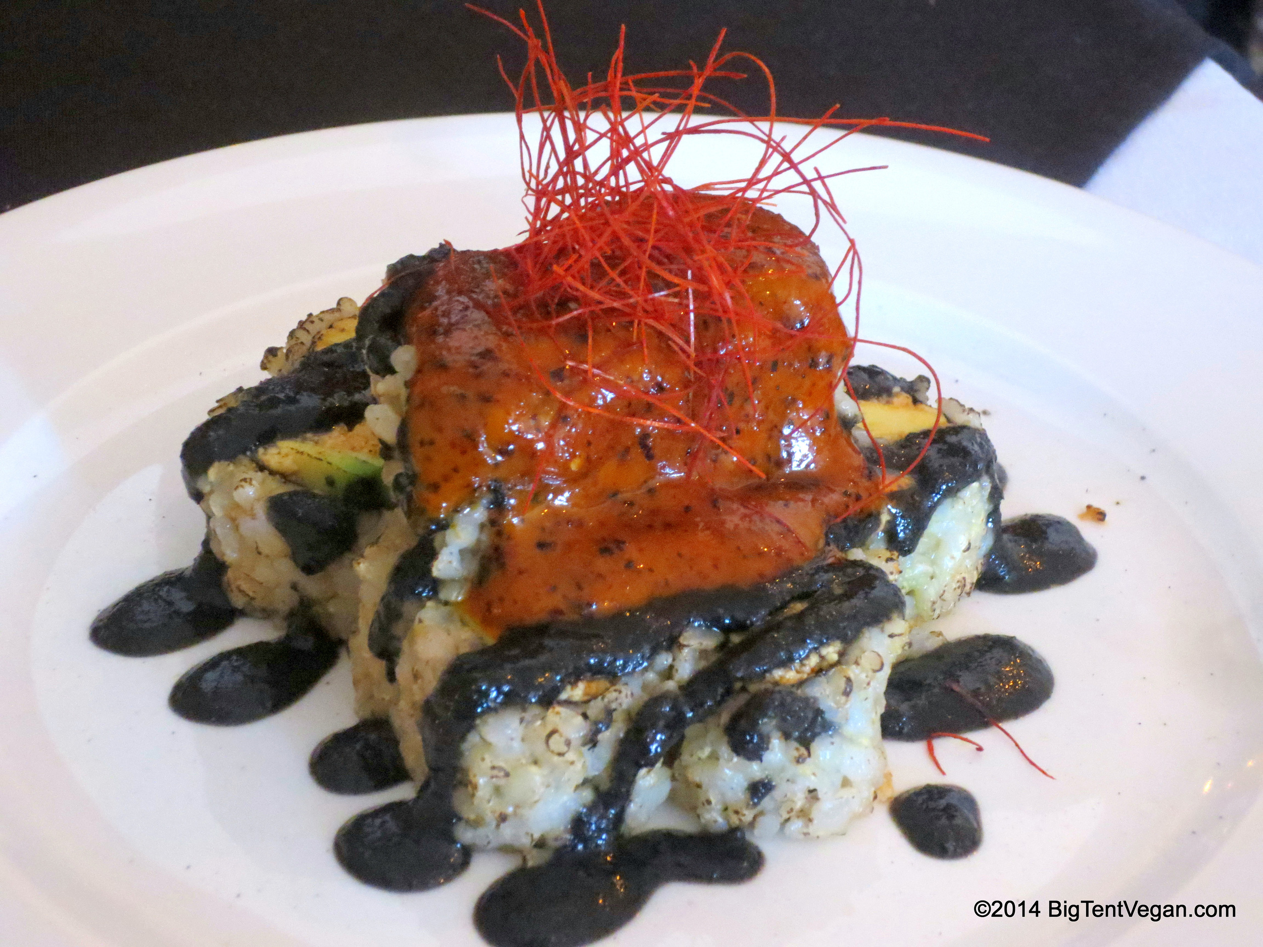 """Black Volcano: Spicy """"Tuna"""" (tofu) and Avocado Roll, topped with house-made Black Sesame Tahini Sauce and Spicy Chili Mayo, garnished with delicate threads of Cayenne Pepper."""
