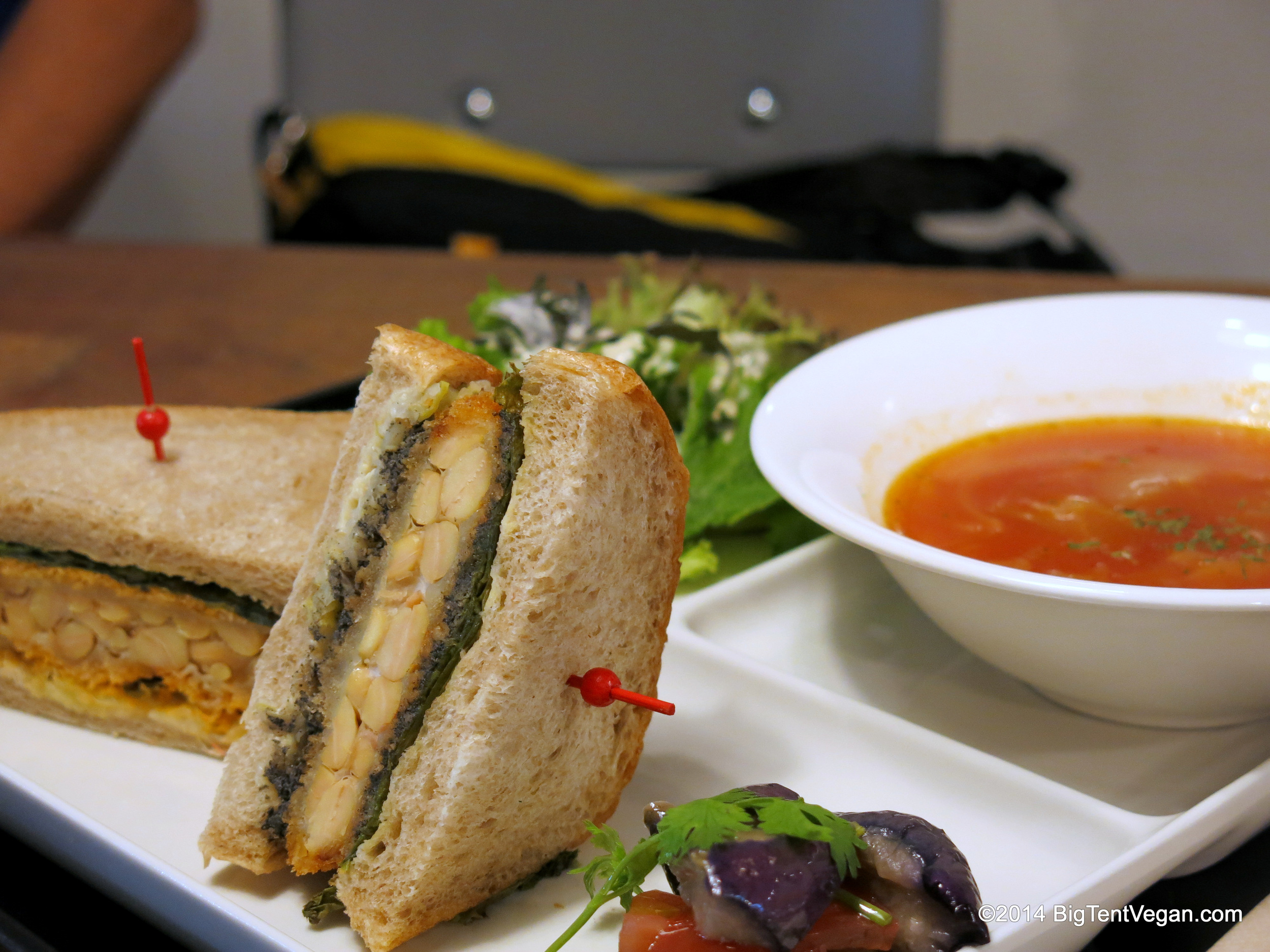 Deep-fried Crispy Tempeh Sandwich with Fresh Green Salad, Tomato Soup, and Pickled Eggplant. Notice each half-sandwich came with a different spread...one had a green pesto spread, and the other a pinkish tomato spread.