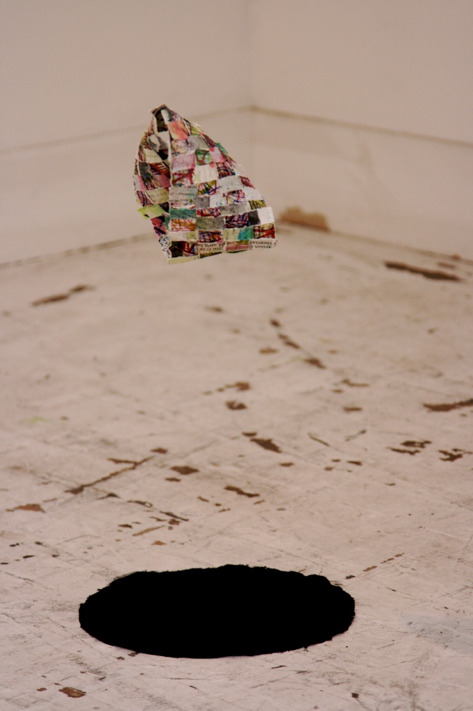 Nothing turns itself inside out.  Handmade, printed paper strips in woven möbius form, black silk cloth. 2008.