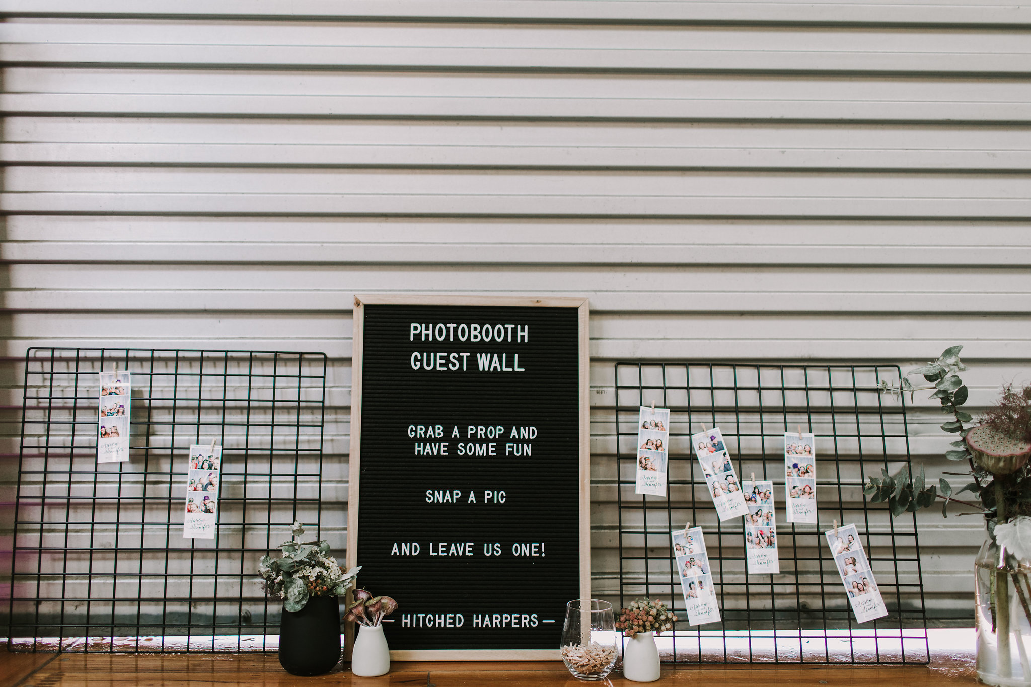 Add a creative element to your reception with a photo booth guest wall. Image credit:  Anitra Wells Photography.