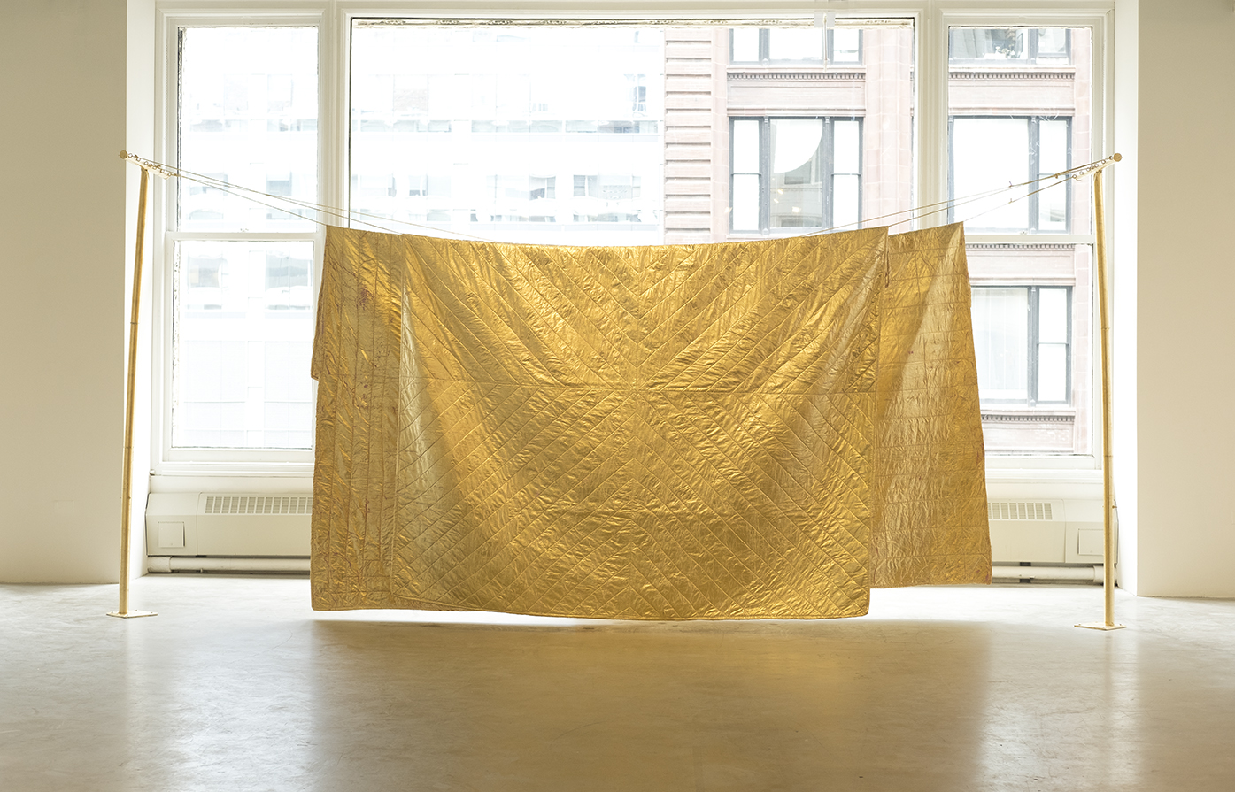 Three gold leafed, machine sewn, hand dyed quilts. Three lengths of gold leafed cotton clotheslines rope. Two gold leafed galvanized steel clothesline poles.